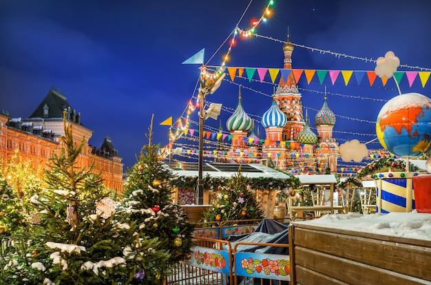 Bandeiras e outras decorações de ano novo da praça vermelha em moscou e da catedral de são basílio em uma noite de inverno
