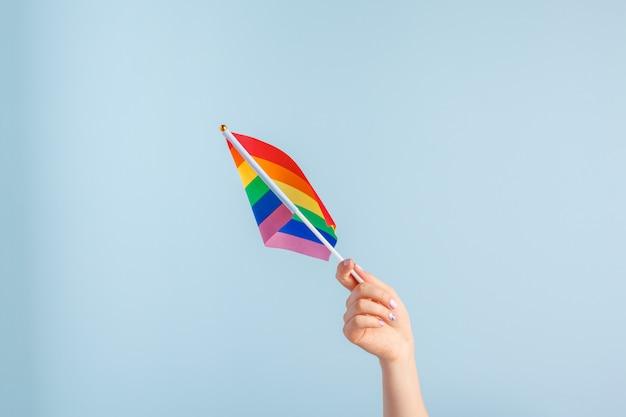 Bandeiras gays na mão das mulheres em fundo cinza