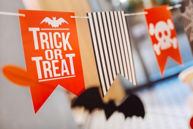 Bandeiras laranja. perto de pequenas bandeiras laranja brilhantes com um sinal de doce ou travessura para a festa infantil de halloween