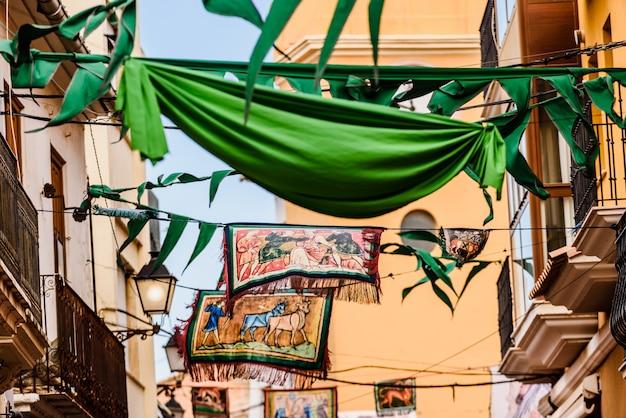 Bandeiras medievais que penduram entre ruas em um festival ao ar livre.