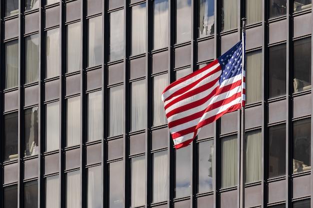 Bandeiras nacionais americanas sobre a paisagem urbana de edifício de chicago