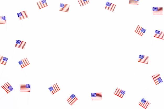 Bandeiras pequenas dos eua espalhadas no fundo branco