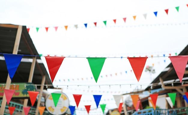 Bandeiras triangulares coloridos que penduram entre a casa velha do vintage.