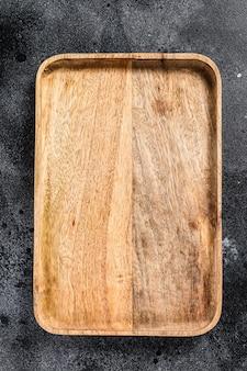 Bandeja antiga de madeira. plano de fundo texturizado preto. vista do topo. copie o espaço