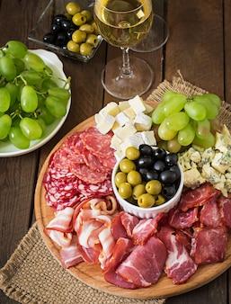 Bandeja antipasto de catering com bacon, carne seca, salame, queijo e uvas
