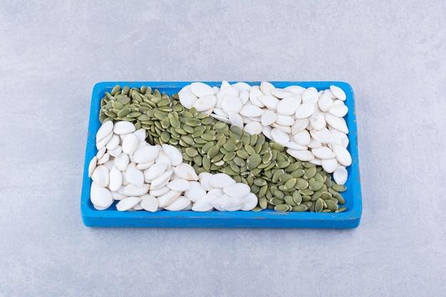 Bandeja azul cheia de sementes de abóbora brancas e pepitas na superfície de mármore