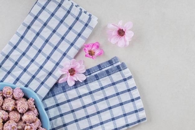 Bandeja azul de doces de pipoca em uma toalha cuidadosamente dobrada ao lado de uma linha de flores na mesa de mármore.