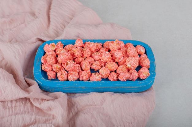 Bandeja azul em uma toalha de mesa, cheia de pipoca revestida de doces na mesa de mármore.