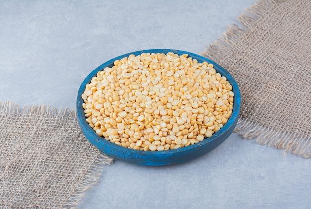 Bandeja azul gasta cheia de lentilhas em pedaços de tecido com fundo de mármore.