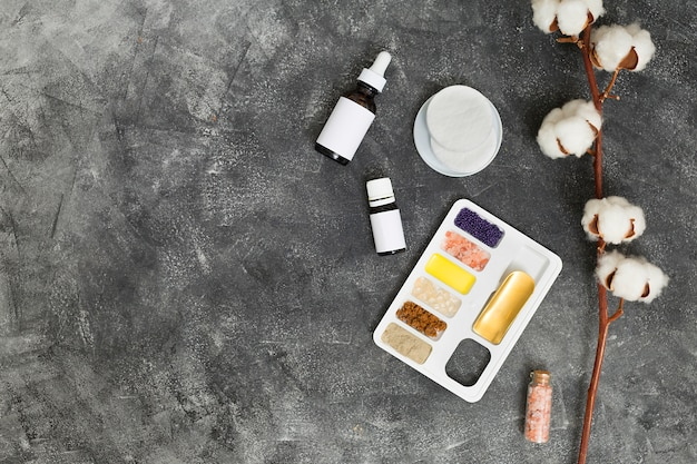 Bandeja branca com argila rhassoul; grãos de café; óleo; garrafas de sal e óleo essencial de rocha com almofadas de algodão e algodão sobre o fundo de concreto preto