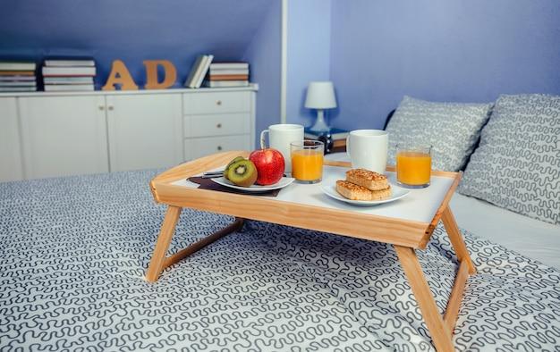 Bandeja cama com café da manhã para duas pessoas em uma cama de casal em um quarto