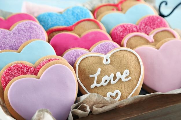 Bandeja com biscoitos do amor na superfície da mesa de madeira azul