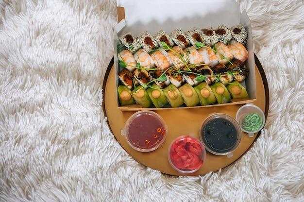 Bandeja com caixa de sushi e molhos em um tapete branco em casa.