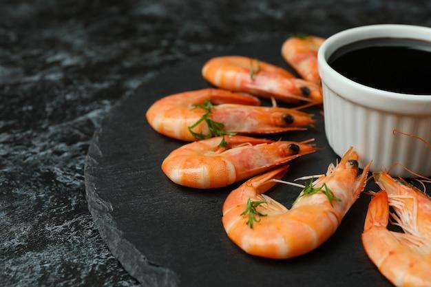 Bandeja com camarão e molho de soja em fundo preto esfumaçado