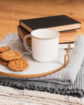 Bandeja com cookied e leite e pilha de livros