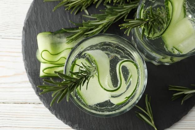 Bandeja com copos de água de pepino na mesa de madeira