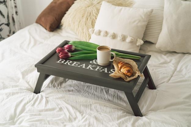 Bandeja com croissant, xícara de café e tulipa na cama branca e limpa.