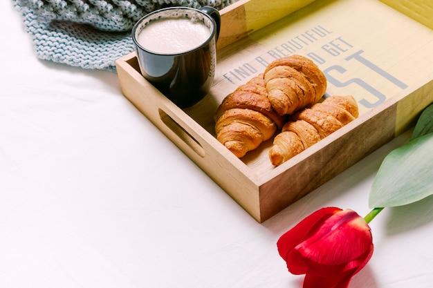 Bandeja com croissants e copo de leite na cama de luz
