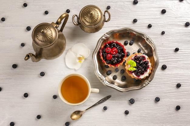 Bandeja com deliciosos bolos e xícara de chá na mesa branca