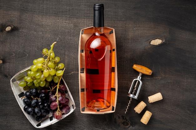 Bandeja com garrafa de vinho e uvas orgânicas