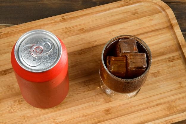 Bandeja com lata de refrigerante de alumínio e copo cheio de gelo