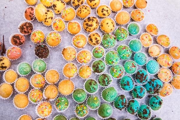 Bandeja com muffins pequenos com cobertura colorida.