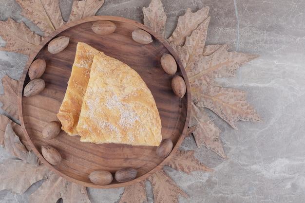 Bandeja com noz-pecã e fatias de pão achatado feseli em mármore