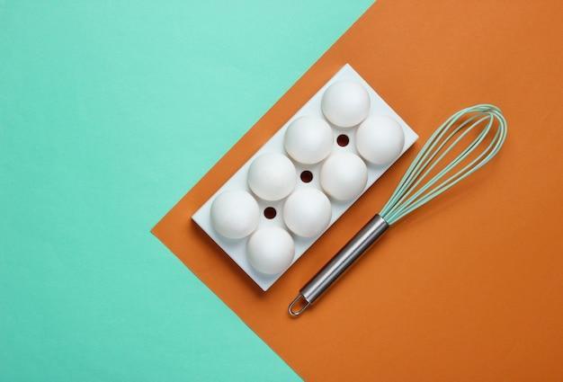 Bandeja com ovos de galinha brancos e bata no colorido