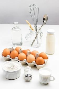 Bandeja com ovos marrons e tigela de farinha. duas garrafas de leite e água. batedor de metal e colher em frasco de vidro. vista superior
