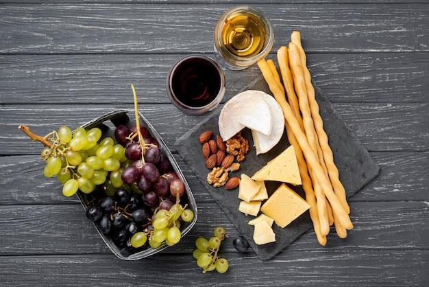 Bandeja com queijo e uvas ao lado de copo com vinho