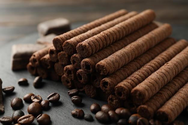 Bandeja com rolinhos de wafer de chocolate, grãos de café e chocolate, close-up