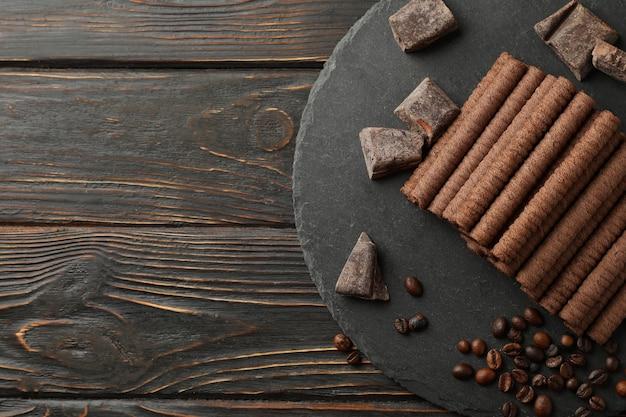 Bandeja com rolinhos de wafer de chocolate, grãos de café e chocolate em madeira