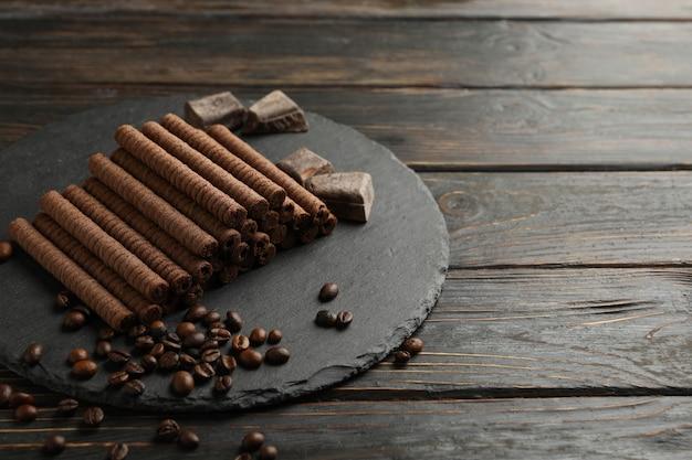 Bandeja com rolos de wafer de chocolate, grãos de café e chocolate no fundo de madeira