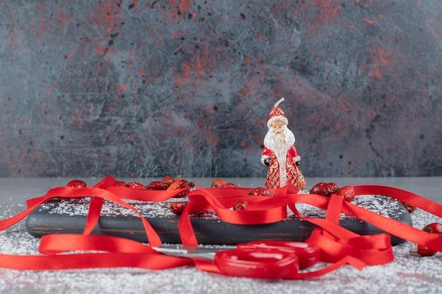 Bandeja com rosas de cachorro, fitas vermelhas, tesouras, pó de coco e estatueta de papai noel na superfície de mármore