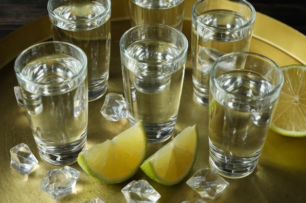 Bandeja com shots, rodelas de limão e cubos de gelo, close-up