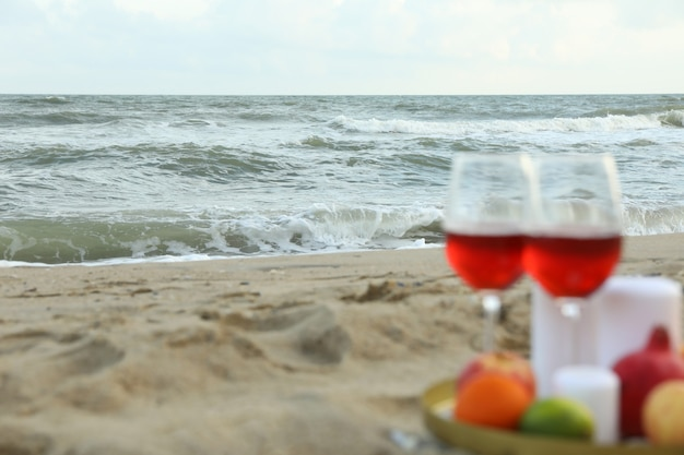 Bandeja com taças de vinho, frutas e velas na areia da praia