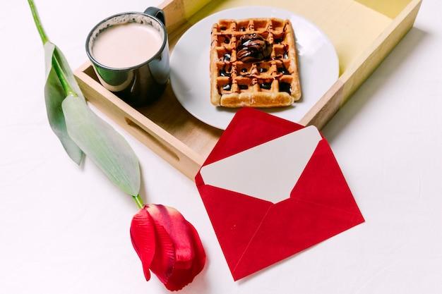 Bandeja com waffle belga e copo de leite na cama de luz