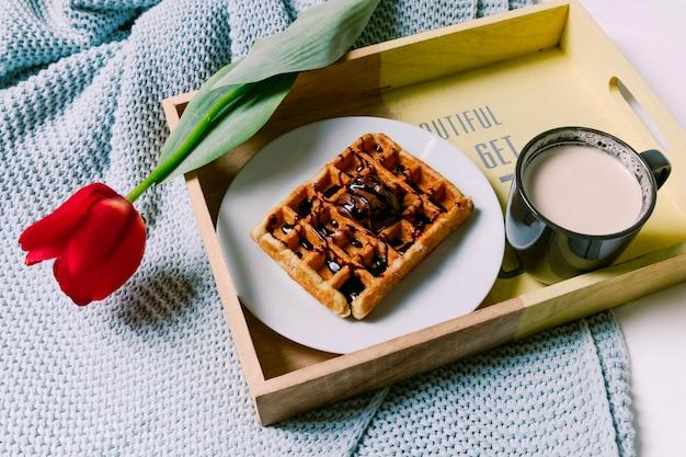 Bandeja com waffle belga e copo de leite no cachecol