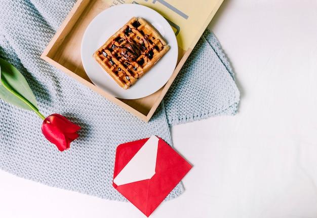 Bandeja com waffle belga e tulipa vermelha no cachecol