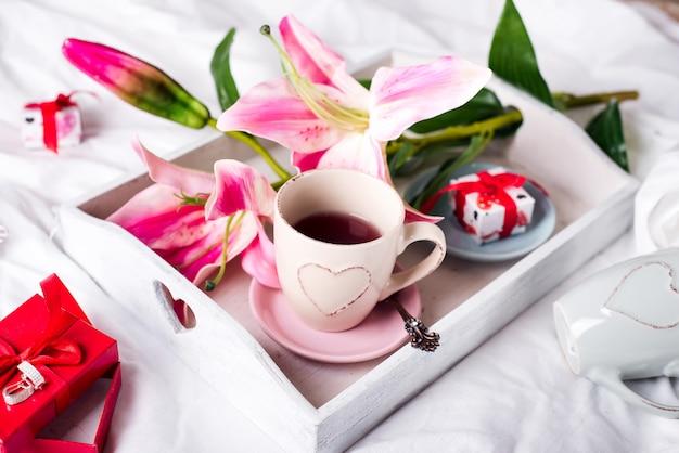 Bandeja com xícara de chá quente na cama