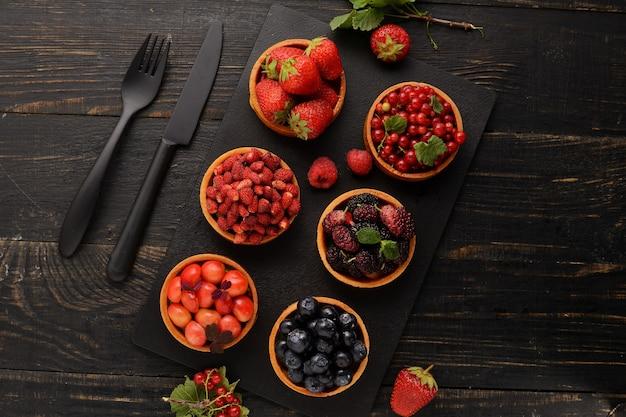 Bandeja da sobremesa das tartlets da fruta e da baga assorted.