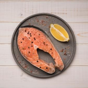 Bandeja da vista superior com bife de salmão cru e limão