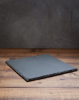 Bandeja de ardósia em mesa de madeira, com textura de fundo de parede