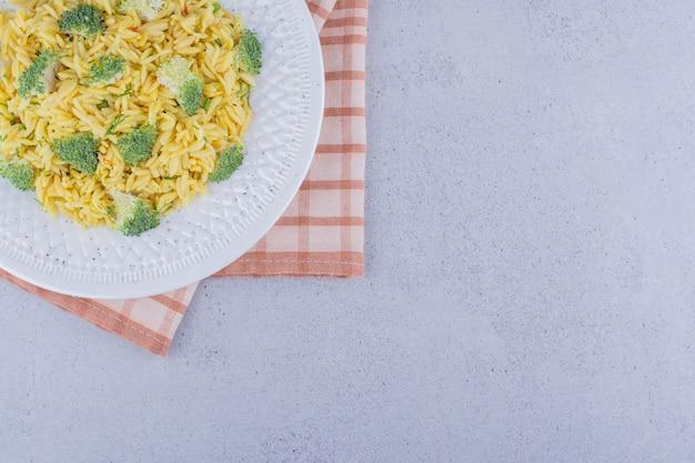 Bandeja de arroz integral cozido com cobertura de brócolis no fundo de mármore.