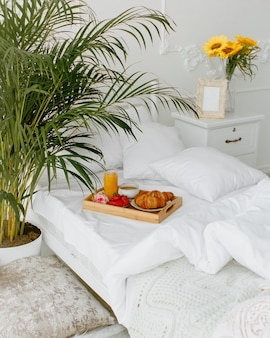 Bandeja de café da manhã colocada na cama de solteiro com roupa de cama branca