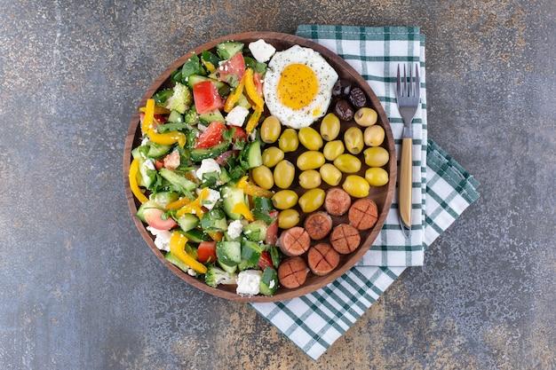 Bandeja de café da manhã com ovos fritos e salada de legumes