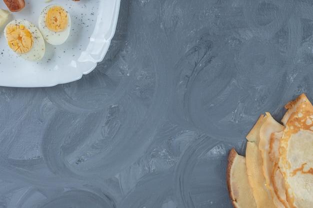 Bandeja de café da manhã e panquecas alinhadas de forma oposta na mesa de mármore.