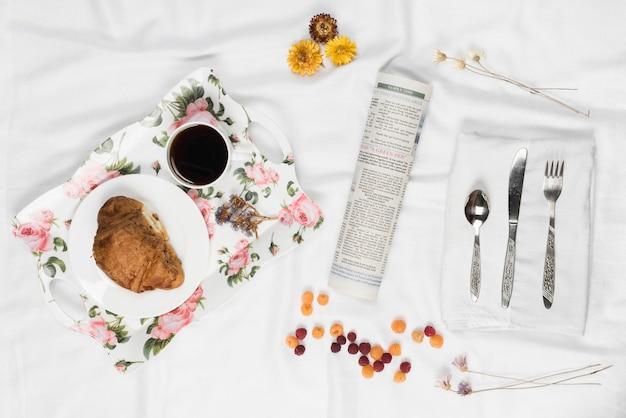 Bandeja de café da manhã floral; framboesa; jornal enrolado; flor e talheres em guardanapo branco sobre o pano de cetim