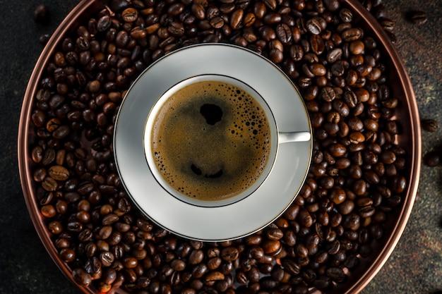 Bandeja de cobre redonda com grãos de café kopi luwak, branca xícara de café com pires na superfície escura, vista superior, closeup