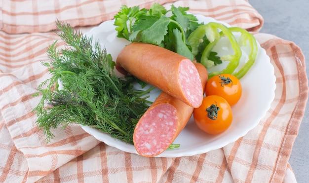 Bandeja de comida com delicioso salame, tomate, salada e vegetais.